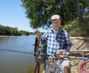 Eldery man with his catfish