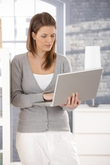 Woman standing with laptop at home