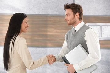 Young businesspeople greeting each other smiling