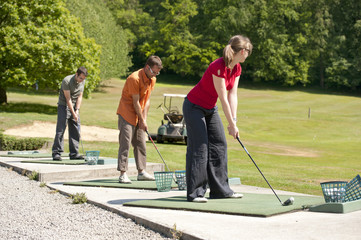 golfers inline at the driving range