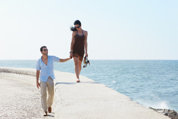 young husband and wife during afternoon walk near the sea
