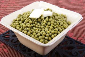 Cooked peas with butter in a ceramic dish