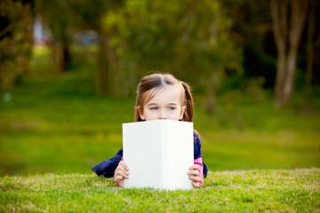 A little girl comtemplating her reading outside.