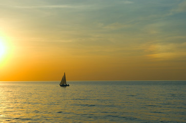 Yacht sailing on the sea, to meet the sunset