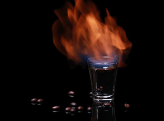Flaming Sambuca surrounded by coffee beans on black