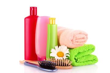 Shampoo bottles and hair brush on white