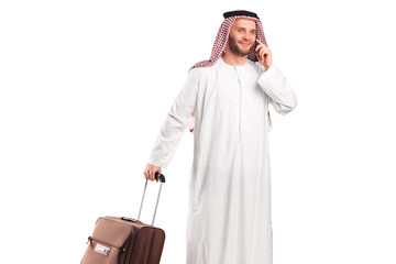 Arab tourist carrying a suitcase and talking on a mobile phone