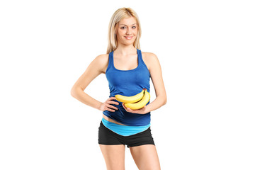 Portrait of a female athlete holding bananas