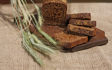 Bread rye cut with slices and ripe ears.