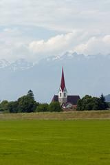 Kirche vor Alpenhintergrund