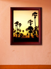 Sunset palm trees in wooden frame