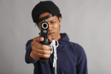 Young woman dressed like a gangster with pistol.
