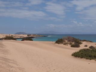 Sandbucht eines Badestrandes mit einem Berg im Hintergrund