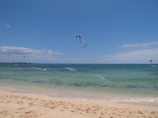 Strand mit Kitesurfer im Hintergrund