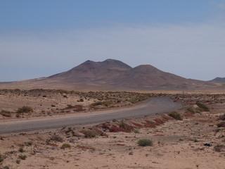 Straße im Nirgendwo mit Gebirge im Hintergrund