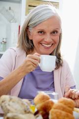 Glückliche Seniorin beim Früstück