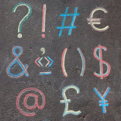punctuation marks and currency symbols drawn on asphalt