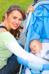 Smiling mother sitting near stroller and taking care about baby.