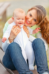 Happy mother holding smiling adorable baby girl in hands.