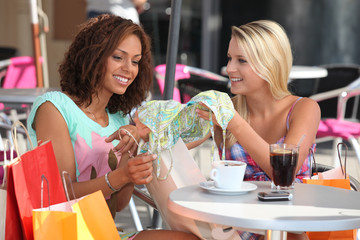 Friends comparing purchases in a cafe