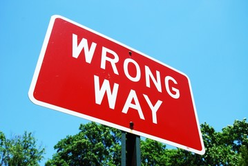 wrong way road sign on a blue sky background