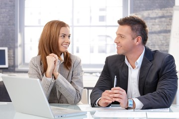 Happy businesspeople smiling at each other