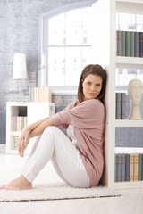 Attractive woman posing by bookcase