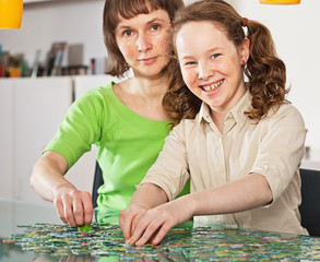 Teenager girl assembling jigsaw with her mother