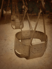 Empty toddler swing in a park with vintage grunge texture