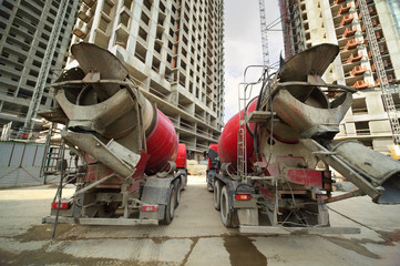 Two concrete mixer stand near unfinished tall high-rise building