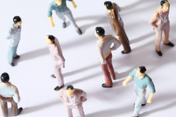 miniature toy mans stand in different poses on white