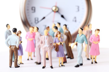 miniature toy people stand in different poses near alarm clock