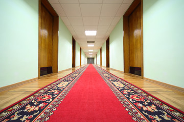 long hallway with brown wood doors, end of corridor, carpet