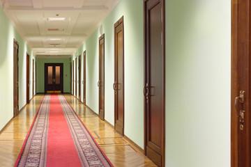 long hallway with brown wood doors, door at end of corridor