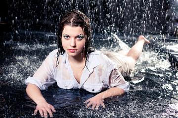 beautiful girl in the rain against a dark background
