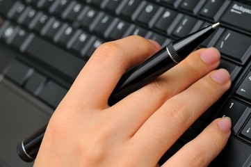Hand holding pen and typing