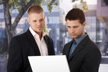Two businessmen with laptop outside of office