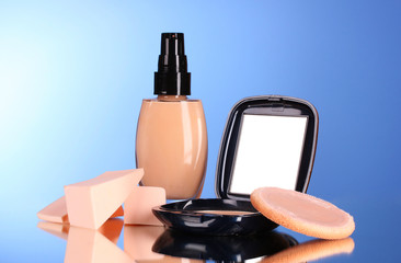 concealer, face powder and sponges on a blue background