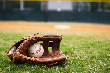 Old Baseball and Glove on Field