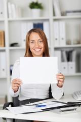 glückliche frau im büro zeigt weißes schild