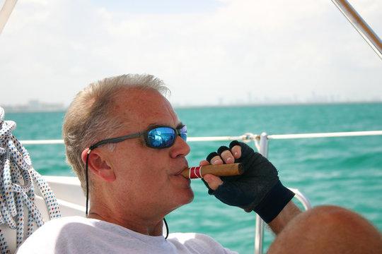 Middle-aged man smoking cigar on sailboat