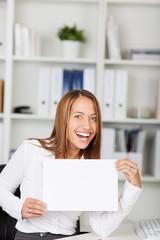 lachende frau zeigt ein schild im büro