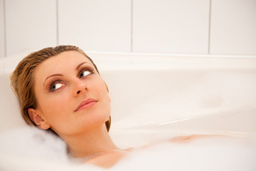 Woman is relaxing in a bathtub