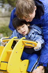 Father helping disabled son play on playground equipment