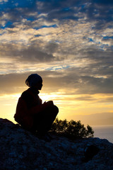 Silhouette of a woman on top of the mountain at the sea while su