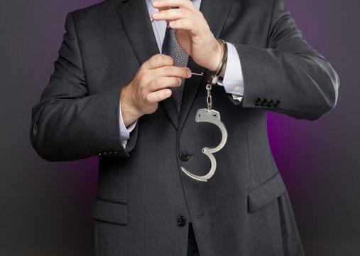 Businessman unlocking handcuffs