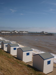 Beach huts Southwold with pier in back ground