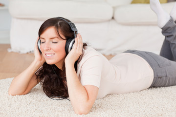 Cute brunette woman using headphones while lying on a carpet