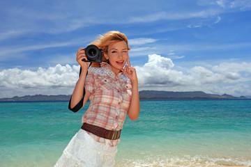ビーチでカメラを楽しむ笑顔の女性