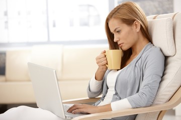 Young woman with laptop drinking tea